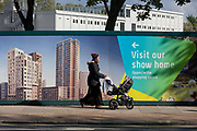 A mother walks past a regeneration project hoarding at Elephant Park, Elephant & Castle, on 11th October 2016, in London, England. Southwark Council's development partner, Lendlease is regenerating over 28 acres across three sites at the heart of Elephant & Castle, in what is the latest major regeneration opportunity in zone 1 London. The vision for the £1.5 billion regeneration is to build on the area's strengths and vibrant character in order to re-establish Elephant & Castle as one of London's most flourishing urban quarters. The Elephant & Castle regeneration is of a scale rarely seen in central London and includes almost 3,000 new homes, plus office, retail, community, leisure and restaurant space.