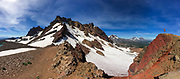 A lone hiker is dwarfed by the vast mountain panorama in front of him at Broken Top saddle, overlooking the Three Sisters in the Central Oregon Cascade Range.