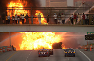 Bystanders on a pedestrian overpass watch as smoke and flames rise from a tanker fire on I-75 in southwest Detroit. 13,400 gallons of gasoline burned.