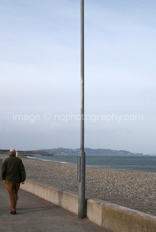 Man walking along the seafront at the seaside town of Bray in Wicklow Ireland