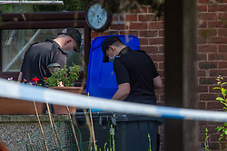 © Licensed to London News Pictures. 21/05/2020. Beaconsfield, UK. Specialist search team members search through bins at a property on North Drive. Thames Valley Police were called to North Drive, Beaconsfield at around 00:01 BST on Thursday 21/05/2020 to a report of a stabbing. A man in his forties had sustained injuries consistent with stab wounds and was taken to hospital. Photo credit: Peter Manning/LNP