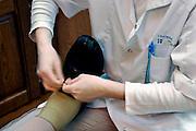 Nederland, Nijmegen, 30-3-2006Een verpleegkundige van de thuiszorg doet haar ronde en helpt een oudere vrouw, die nog zelfstandig woont, met haar schoenen.Foto: Flip Franssen