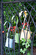 Black wrought iron garden gate with three colorful flower pots