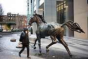 Bronze horses created by British sculptor Hamish Mackie galloping through water in the public square at Goodman's Fields in Aldgate on 24th February 2020 in London, United Kingdom.