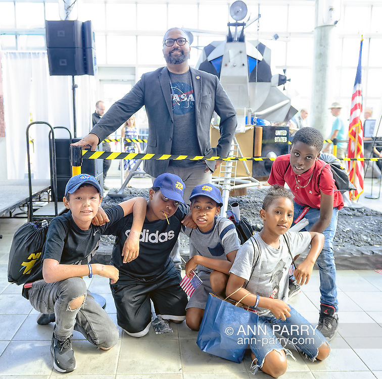 Garden City, New York, U.S. July 20, 2019.  At top, New York State Senator KEVIN THOMAS poses with children from Westbury who attended the Moon Fest Apollo at 50 Countdown Celebration at Cradle of Aviation Museum in Long Island, held during the same time Apollo 11 Lunar Module landed on the Moon 50 years ago.