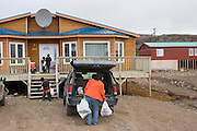 """Pauline Melanson unloading groceries in front of her family home, in Iqaluit, Nunavut, Canada. The Melanson family consists of Peter, Pauline, Joseph, Jacob, and Shane. They live one street off """"The Road To Nowhere,"""" on a hill overlooking the town of Iqaluit in Canada's northeastern territory of Nunavut (just south of the Arctic Circle)."""