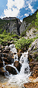 A stream tumbles in a waterfall from Sella massif (Gruppo di Sella), down to Corvara, a prestigious tourist center in Alta Badia, in Val/Valle/Valley of Badia in the province of Südtirol/South Tyrol/Alto Adige, Italy. Corvara is surrounded by the peaks of the Dolomites (or Dolomiti), a part of the Southern Limestone Alps in Europe. The Dolomites were declared a natural World Heritage Site (2009) by UNESCO. Panorama stitched from 3 overlapping photos.