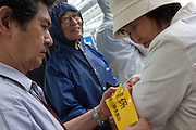 Communist Party members prepare armbands before Shii Kazuo, the leader of the Japansese Communist Party (Nihon Kysant) ,campaigns in Yokohama, Kanagawa, with candidate, Kimie Hatano in Yokohama, Kanagawa, Japan, July 9th 2010