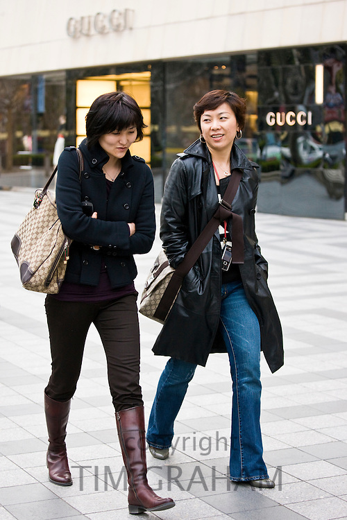 Chinese women pass Gucci shop, in Nanjing Road designer shopping district, central Shanghai, China