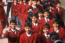 Group of school boys and girls wearing crimson uniform taking part in school trip,