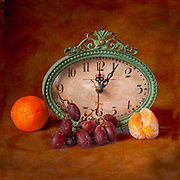 Still life of antique clock with fruit.