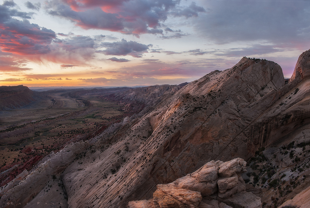 """""""Unsettled""""<br /> (The Waterpocket Fold, Utah)<br /> I am restless.  All of these precious days in the desert I have been driven.  Pushing myself to see, often with a vague sense of what I want to find, to discover with my own eyes.  Up before sunrise, I find myself resenting a forced rest after sunset, when my thoughts are not distracted by the sight of real canyons, and they find their way down darker ones.  Why is it in the night that I become the most troubled…that I wonder if I make too much of dreams, too much of words, too much of love.  I mourn the failures I have made, the failures I am still making.  Overnight, the skies over this part of Utah became unsettled, matching my mood.  At dawn I am standing on top of a sharp monocline, surrounded by 60 million years of geology.  A prism of light graces storm clouds dropping elegant veils of virga--a trail of tears in a land of drought.  I have sought wild places, isolated and lonely, and yet I expect to be loved.  It is a curious dichotomy.  Maybe they are meant to be seen alone, to be loved in solitude so that you can put other feelings in perspective.   I need moments like this to carry as a mental cache of calmness, to be summoned as last thoughts before sleep."""