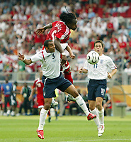 Photo: Chris Ratcliffe.<br /> England v Trinidad & Tobago. Group B, FIFA World Cup 2006. 15/06/2006.<br /> Ashley Cole from England clashes with Brent Sancho  from T&T.