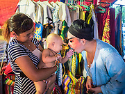 "14 MAY 2015 - BANGKOK, THAILAND:    A Chinese opera performer greets a mom and her baby backstage before a show at the Pek Leng Keng Mangkorn Khiew Shrine in the Khlong Toey slum in Bangkok. Chinese opera was once very popular in Thailand, where it is called ""Ngiew."" It is usually performed in the Teochew language. Millions of Chinese emigrated to Thailand (then Siam) in the 18th and 19th centuries and brought their culture with them. Recently the popularity of ngiew has faded as people turn to performances of opera on DVD or movies. There are still as many 30 Chinese opera troupes left in Bangkok and its environs. They are especially busy during Chinese New Year and Chinese holiday when they travel from Chinese temple to Chinese temple performing on stages they put up in streets near the temple, sometimes sleeping on hammocks they sling under their stage. Most of the Chinese operas from Bangkok travel to Malaysia for Ghost Month, leaving just a few to perform in Bangkok.     PHOTO BY JACK KURTZ"