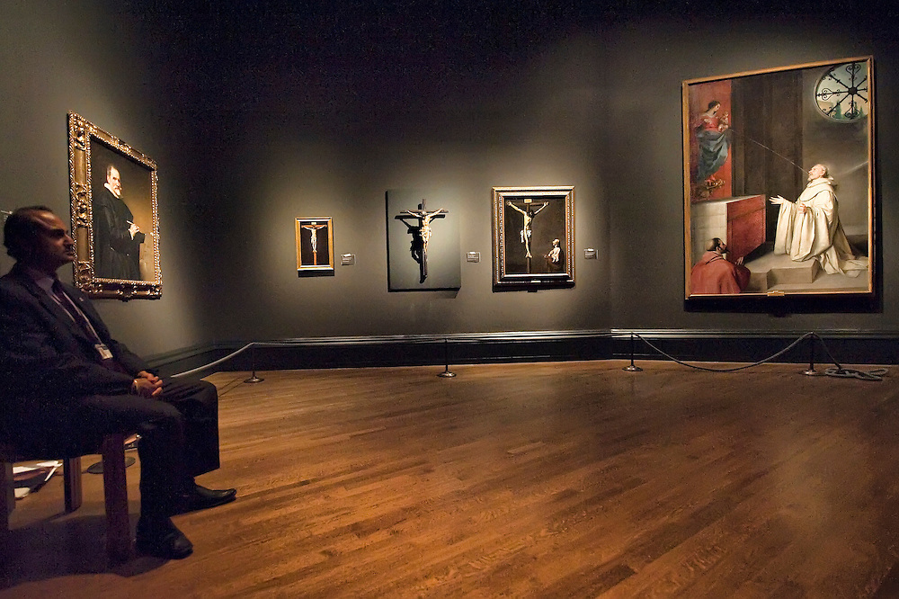 LONDON, ENGLAND - OCTOBER 16:  A National Gallery employee seats next to  three paintings  of Crucifixion by (L-R) Francisco Paceco,  Juan de  Mesa and Francisco de Zurbaran at 'The Sacred Made Real Exhibition' at the National Gallery  on October 16, 2009 in London, England. The Exhibition running from October 21 to January 24, 2010 includes masterpieces by Velasquez and Francisco de Zurbaran which are displayed for the very first time alongside Spain's polyccrome painted sculptures  ...***Agreed Fee's Apply To All Image Use***.Marco Secchi /Xianpix. tel +44 (0) 771 7298571. e-mail ms@msecchi.com .www.marcosecchi.com