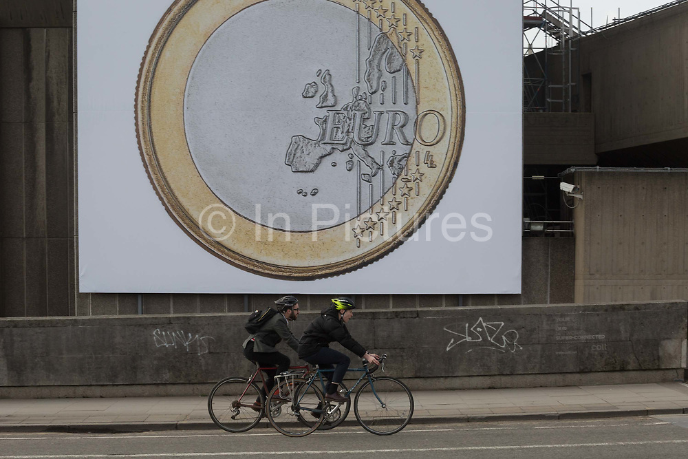 Cyclists pedal past a giant Euro coin, an artwork by Danish artists Superflex, hanging from the hayward Gallery on Waterloo Bridge, on 3rd February 2017, London, England. For the third Waterloo Billboard Commission, the work is a euro coin with its value conspicuously absent – made by the group in 2012, in response to the Greek financial crisis – has gained new resonance since the UKs decision to leave the EU. The billboard is the third in a series of large-scale commissions by international artists, occupying the prominent billboard site next to Hayward Gallery.