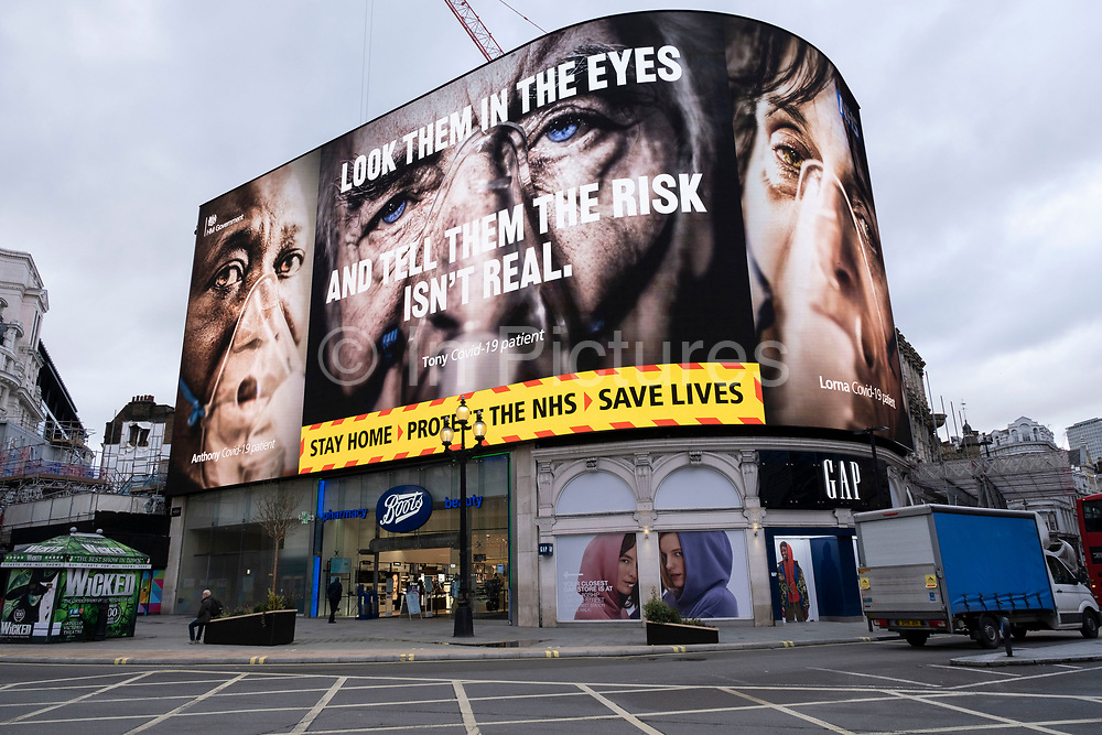 At Piccadilly Circus the giant advertising screens show slogans and the faces of coronavirus patients which are part of the latest NHS, Public Health England campaign to encourage people in Britain to take the virus seriously as the national coronavirus lockdown three continues on 29th January 2021 in London, United Kingdom. Following the surge in cases over the Winter including a new UK variant of Covid-19, this nationwide lockdown advises all citizens to follow the message to stay at home, protect the NHS and save lives.
