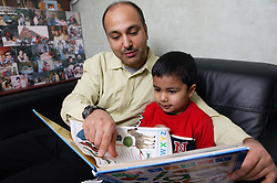 Single parent helping son read a book together on the sofa at home,