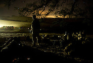 A Marine stands guard as lights from the weapon depot, left, and a rising moon, light up the horizon during live-fire exercises at Camp Pendleton.