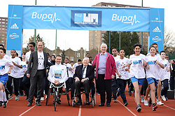 © London News Pictures. 26/02/2014. London, UK. L to R  HUGH BRASHER, Event Director, DAVID IER, Paralympic wheelchair athlete, SIR ROGER BANNISTER, the first man to run a sub-four minute mile and DIANNE CHARLES (formerly Dianne Leather) the first woman to run a sub-five minute mile, at Paddington Recreation ground in London to launch the 2014 Bupa Westminster Mile in May 2014, which will officially celebrate the 60th anniversary. The track at Paddington Recreation ground was where Sir Roger Bannister trained for the record attempt. Photo credit: Mike King/LNP