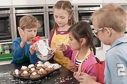 Students sprinkle powdered sugar on muffins in home economics class, Bavaria, Germany