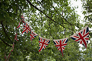 Union Jack bunting hangs in the trees of a London park, on 24th June 2017, in Ruskin Park, the south London borough of Lambeth, England. Bunting is a festive decoration made of fabric, or of plastic, paper or even cardboard in imitation of fabric. Typical forms of bunting are strings of colorful triangular flags and lengths of fabric in the colors of national flags gathered and draped into swags or pleated into fan shapes. The term is also used to refer to a collection of flags, and particularly those of a ship. The officer responsible for raising signals using flags is known as bunts, a term still used for a ships communications officer.
