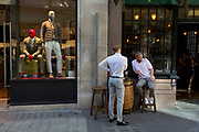 Two young men enjoy drinks outside a pub next to stylishly-dressed menswear mannequins on Lime Street in the City of London, the capital's historic financial district, on 2nd August 2018, in London, England.