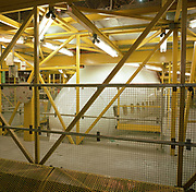 During a lull in activity, a Boeing 747 is swathed in engineering gantries during a major check (maintenance schedule) at the British Airways Heathrow base in London England. As if in a hospital ER several metres off the ground, yellow struts surround the aircraft's forward nose section and the first class windows along the white fuselage allowing mechanics, engineers and avionics specialists unimpeded access to every element of the air frame. Neon tubes illuminate the hangar that houses flying machines which are serviced here between transcontinental commercial passenger flights. Picture from the 'Plane Pictures' project, a celebration of aviation aesthetics and flying culture, 100 years after the Wright brothers first 12 seconds/120 feet powered flight at Kitty Hawk,1903.