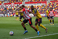 Brentford Forward Bryan Mbeumo(#19) shields the ball from Watford defender Christian Kabasele (27) during the EFL Sky Bet Championship match between Brentford and Watford at Brentford Community Stadium, Brentford, England on 1 May 2021.