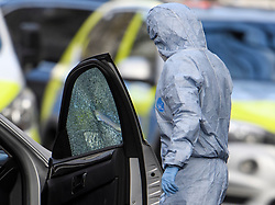 © Licensed to London News Pictures. 13/04/2019. London, UK. A police forensics officer examines broken glass and a bullet hole on a car at the scene in Holland Park after shots were fired near the Ukrainian embassy. Photo credit: Ben Cawthra/LNP