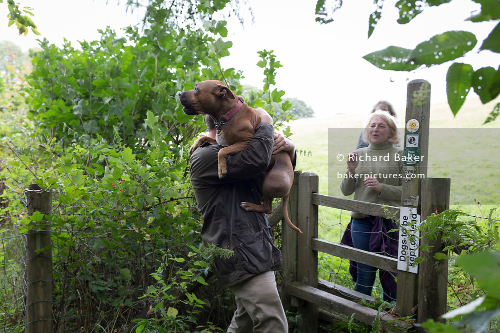A dog owner carries his pet over a countryside stile, on 10th September 2018, near Lingen, Herefordshire, England UK.