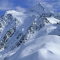 Skier descends Shukson Arm in the Mount Baker Wilderness near Washington's Mount Baker Ski Area. Mount Shuksan rises in the background.