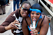 A woman with a vibrator jokes around at Notting Hill Carnival in West London. The Notting Hill Carnival is an annual event which sinc at e 1964 has taken place each August, over two days (the August bank holiday Monday and the day beforehand). It is led by members of the West Indian / Caribbrean community, particularly the Trinidadian and Tobagonian British population, many of whom have lived in the area since the 1950s. The carnival has attracted up to 2 million people in the past, making it the second largest street festival in the world. The celebration centres around a parade of floats, dancers and sound systems.