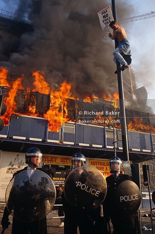 Several metres above the ground, a lone protester hangs on to a street light pole in London's Trafalgar Square at the height of the famous Poll Tax Riot on 31st March 1990 as flames erupt from a building site on The Strand. Three police officers wearing helmets and riot shields brace themselves for further violence as angry crowds, demonstrating against Margaret Thatcher's local authority tax, stormed the Whitehall area and then London's West End, starting fires and overturning cars, looting stores up Charing Cross Road and St Martin's Lane. The anti-poll tax rally in central London erupted into the worst riots seen in the city for a century. Forty-five police officers were among the 113 people injured as well as 20 police horses. 340 people were arrested.