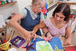 Carer assisting teenage girl to use dual control training scissors in residential respite care home,