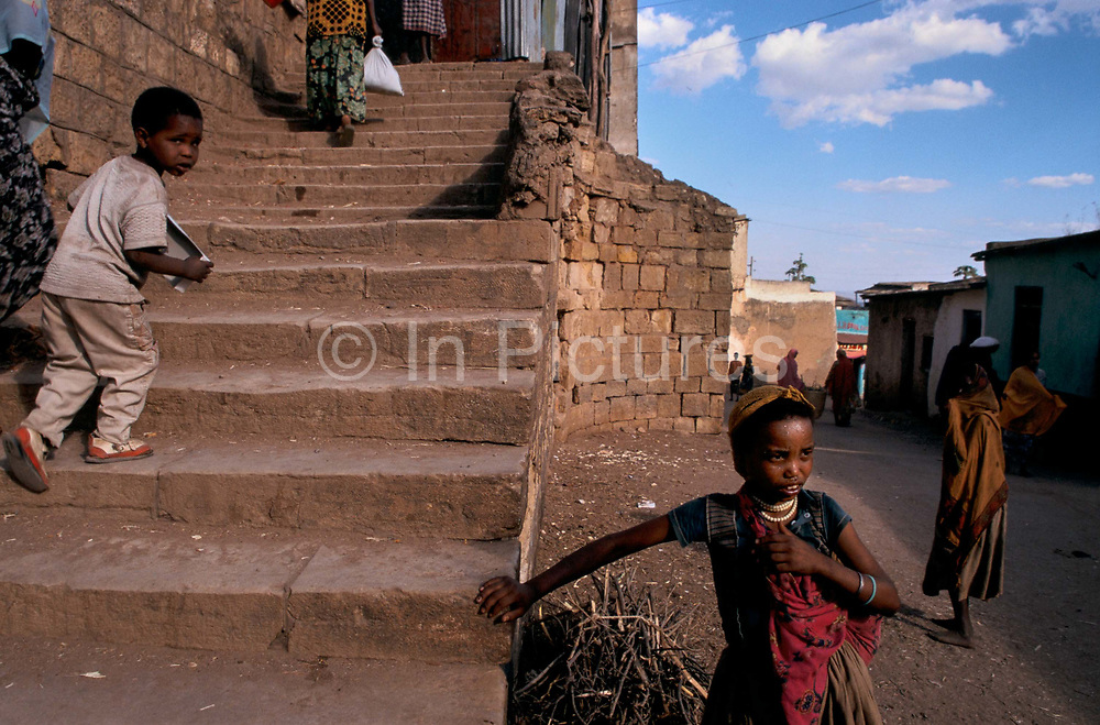 Children sitting on a wall in the ancient walled city of Harar. Situated in Eastern Ethiopia it is considered to be the fourth  holiest city in Islam with 82 mosques. It is a major commercial centre linked by trade routes with the rest of Ethiopia and the entire Horn of Africa.  Ethiopia