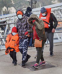 © Licensed to London News Pictures. 14/04/2021. Dover, UK. A migrant family come ashore after being helped by Border Force officials at Dover Harbour in Kent after crossing the English Channel. Home Secretary Priti Patel has pledged an overhaul of asylum seeker rules, with refugees having their claim assessed based on how they arrive in the UK. Photo credit: Stuart Brock/LNP