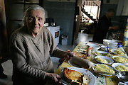 In her farmhouse kitchen in the village of Adamka, in central Poland, 93-year-old Maria Kwiatkowska, Borys's grandmother, slices the cheesecake she baked for the traditional family gathering on All Saints Day. After visiting the graves of their relatives in the local cemetery, her children and grandchildren descend on her for a splendid lunch of noodle soup with cabbage and carrots, pork roast stuffed with prunes, pickled pumpkin, a fruit-nut roll, and cheesecake. Hungry Planet: What the World Eats (p. 250).(MODEL RELEASED IMAGE).
