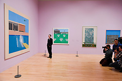 """© Licensed to London News Pictures. 06/02/2017. London, UK. The media photographs a staff member viewing """"A Bigger Splash"""" at the preview of the world's most extensive retrospective of the work of David Hockney at the Tate Britain, which will be on display 9 February to 29 May 2017. Photo credit : Stephen Chung/LNP"""
