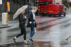 © Licensed to London News Pictures. 19/07/2019. London, UK. A woman shelters from the rain beneath an umbrella in north London. Photo credit: Dinendra Haria/LNP