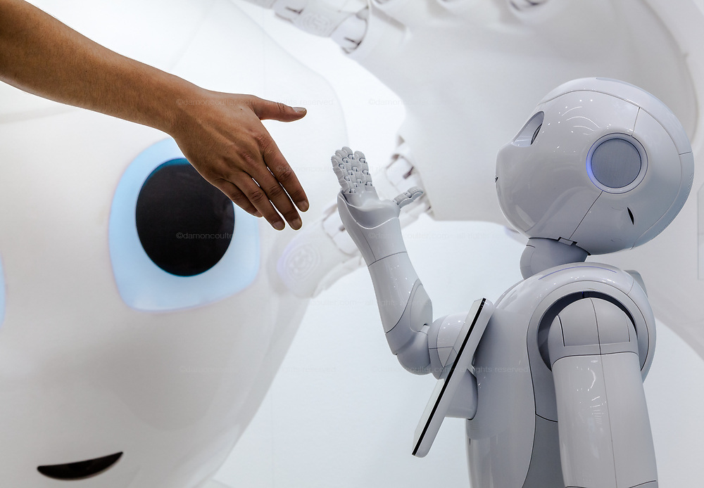 A western tourist interacts with Softbank's emotional consumer Robot, Pepper on display at the Softbank Store Omotesando, Tokyo, Japan. Friday August 1st 2014.  At the end of June 2021 the Softbank company announced it was cutting jobs in its global robotics business and had stopped production of the Pepper robot.