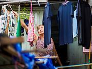 """22 MARCH 2018 - BANGKOK, THAILAND: One of the remaining residents alongside Khlong Lat Phrao hangs her laundry. Bangkok officials are evicting about 1,000 families who have set up homes along Khlong  Lat Phrao in Bangkok, the city says they are """"encroaching"""" on the khlong. Although some of the families have been living along the khlong (Thai for """"canal"""") for generations, they don't have title to the property, and the city considers them squatters. The city says the residents are being evicted so the city can build new embankments to control flooding. Most of the residents have agreed to leave, but negotiations over compensation are continuing for residents who can't afford to move.      PHOTO BY JACK KURTZ"""