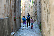 Mother and two daughters wandering through paved, walled streets of Korcula old town. Korcula old town, island of Korcula, Croatia