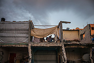 A child is seen in her destroyed house in Khuza's, family are trying to go back to live in their houses