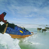 Team crosses over pressure ridge on frozen Great Slave Lake, NWT, Canada.