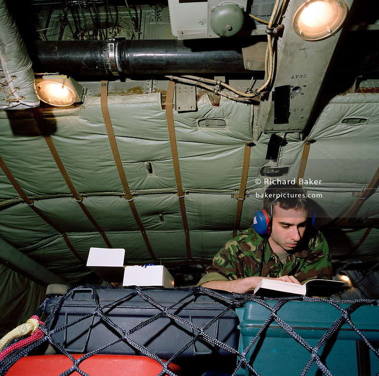 Member of the the elite 'Red Arrows', Britain's prestigious Royal Air Force aerobatic team, spend hours aboard a C-130 Hercules transport aircraft during a two-day journey from RAF Scampton to RAF Akrotiri, Cyprus. The interior is basic with sharp corners but the walls are padded.  Ward wears a heavy camouflaged coat to counteract the cold and ear-plugs from the droning engines. The Red Arrows pilots fly their Hawk jet aircraft to air shows but on long journeys requiring the support of ground crew borrow RAF transporters that fly behind the main airborne squadron shipping 10 tons of spares and personal effects for their six-week winter training stay.