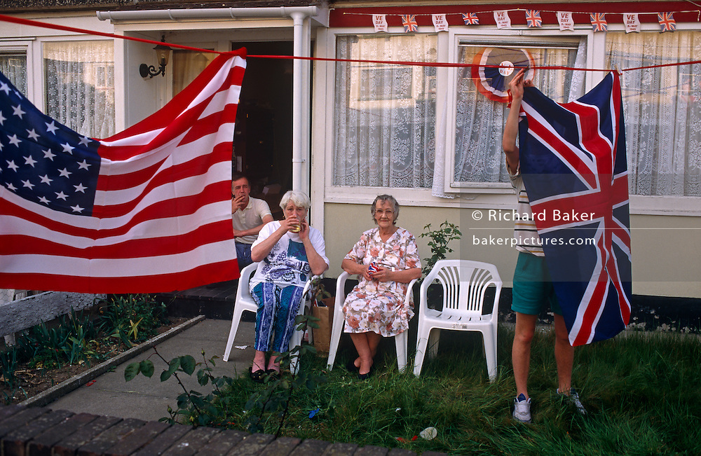 Gathering outside their house in the East End of London, a family sits together to celebrate 50th anniversary of VE (Victory in Europe) Day on 6th May 1995. A man hangs out a Union Jack flag to accompany the Stars and Stripes on a washing line in the front garden. In the week near the anniversary date of May 8, 1945, when the World War II Allies formally accepted the unconditional surrender of the armed forces of Germany and peace was announced to tumultuous crowds across European cities, the British still go out of their way to honour those sacrificed and the realisation that peace was once again achieved. Street parties now - as they did in 1945 - played a large part in the country's patriotic well-being.