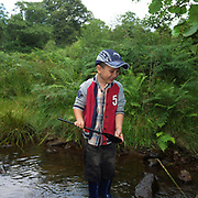 A young boy enjoys pond dipping in a shallow stream, Danby, North York Moors, North Yorkshire, UK