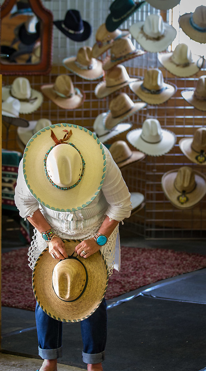 A hat vendor straightens her wares at the Custer County Cowboy Gathering and Chuckwagon Cook Off near Westcliffe, Colo. Presented at Art for the Sangres, double matted in a 14x22 wood frame: $300.