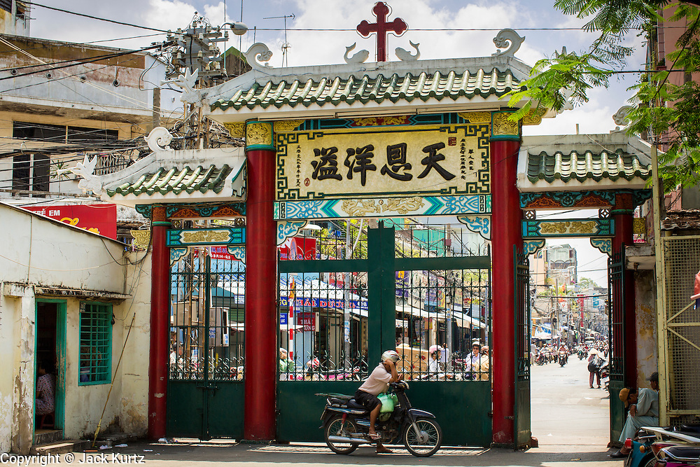 """12 APRIL 2012 - HO CHI MINH CITY, VIETNAM:  Looking out the gate of Cha Tam Catholic Church in Cholon. The church is best known as the last hiding placing of Vietnamese Catholic dictator and US ally, President Ngo Dinh Diem, before he was assassinated in November 1963. Cholon is the Chinese-influenced section of Ho Chi Minh City (former Saigon). It is the largest """"Chinatown"""" in Vietnam. Cholon consists of the western half of District 5 as well as several adjoining neighborhoods in District 6. The Vietnamese name Cholon literally means """"big"""" (lon) """"market"""" (cho). Incorporated in 1879 as a city 11km from central Saigon. By the 1930s, it had expanded to the city limit of Saigon. On April 27, 1931, French colonial authorities merged the two cities to form Saigon-Cholon. In 1956, """"Cholon"""" was dropped from the name and the city became known as Saigon. During the Vietnam War (called the American War by the Vietnamese), soldiers and deserters from the United States Army maintained a thriving black market in Cholon, trading in various American and especially U.S Army-issue items.        PHOTO BY JACK KURTZ"""